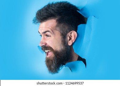 Smiling bearded man watches through hole in paper. Male face through hole in blue paper. Attractive man with beard and mustache breaking paper. Copy space for advertising. Discount, sale, season sales