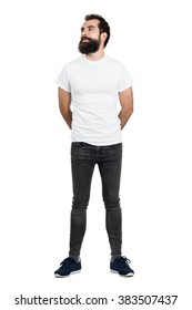 Smiling bearded man wearing white t-shirt and tight jeans looking away. Full body length portrait isolated over white studio background.