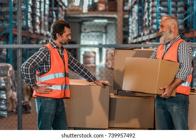smiling bearded mature worker holding box and looking at colleague in warehouse