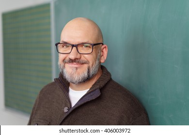 Smiling bearded middle-aged male teacher wearing glasses standing alongside a blank chalkboard in the classroom, close up head and shoulders
