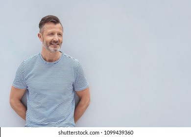 Smiling bearded middle-aged man posing against a rough plaster white wall looking to the side with copy space