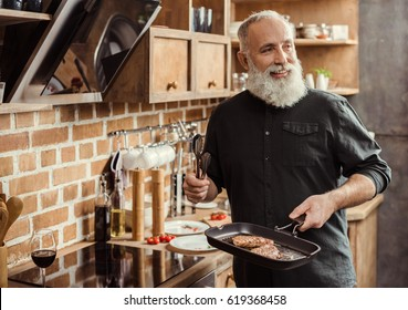 Smiling bearded senior man holding frying pan with steaks and looking away in kitchen