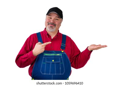 Smiling bearded worker in cap and bib overall holding out his empty hand over blank white copy space pointing to it with a smile of satisfaction