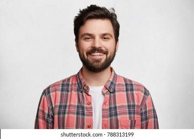 Smiling bearded young male model rejoices coming weekends, dressed casually, isolated over white background. Positive pleased student being in good mood after successfully passed exams at college - Shutterstock ID 788313199