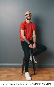 Smiling bearded young man on gray background. Stylish man wearing glasses, looking at camera and laughing while sitting on a tall chair.