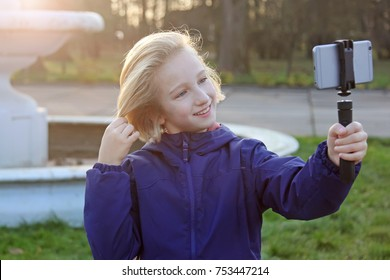 Smiling beatiful preteen girl 9-11 year old taking a selfie outdoors. Child taking a self portrait with mobile phone. Childhood, technology and communication concept.