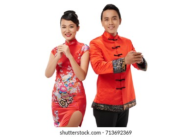 Smiling beautiful Asian couple making hand gesture to congratulate with Tet