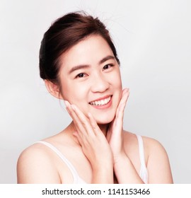 Smiling beautiful asian woman ,Happy Spa Girl Isolated on a gray Background.Touching her Face,young Woman after Bath with Clean Perfect Skin