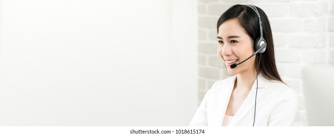 Smiling beautiful Asian woman telemarketing customer service agent working in call center, panoramic banner with copy space
