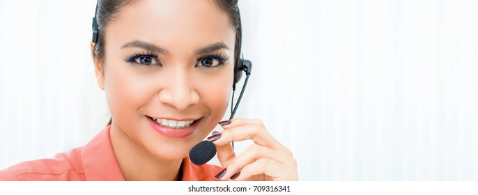 Smiling beautiful Asian woman telemarketing customer service agent in call center - panoramic web banner with copy space