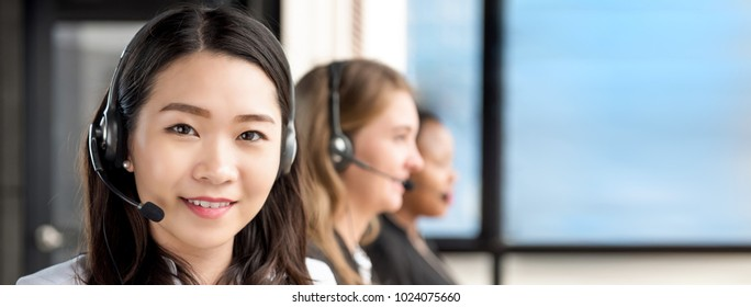 Smiling beautiful Asian woman  working in call center with international team as telemarketing customer service agents, panoramic banner with copy space