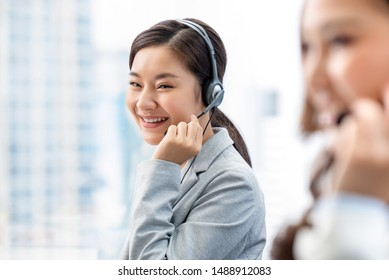 Smiling beautiful Asian woman working in call center office as a customer service operator
