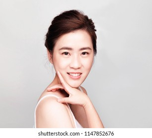 Smiling beautiful asian woman ,young asian girl with clean skin, Cosmetic Beauty Concept,hands touch on the cheek, smiling and friendly face isolated on grey background