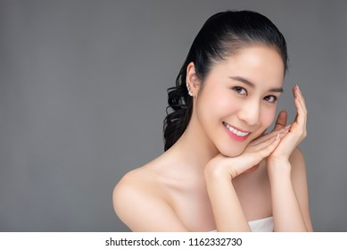 Smiling beautiful Asian woman with youthful radiant face skin for cosmetic and beauty concepts isolated studio shot