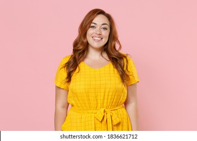 Smiling beautiful attractive young redhead plus size body positive chubby overweight woman in yellow casual dress posing looking camera isolated on pastel pink color wall background studio portrait