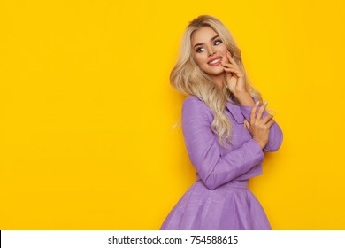 Smiling beautiful blond woman in violet costume is posing and looking away at copy space. Three quarter length studio shot on yellow background.