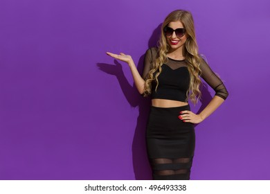 Smiling beautiful blond young woman in black dress and sunglasses posing with hand on hip, presenting something and looking at camera. Three quarter length studio shot on violet background.