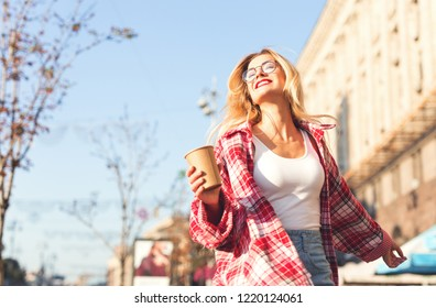 Smiling beautiful blonde womam walking at the street, holding cup of coffee.