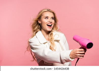 smiling beautiful blonde woman holding hairdryer isolated on pink