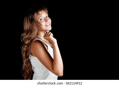 Smiling beautiful blue-eyed blonde girl in white dress on a black background. Cute girl face.