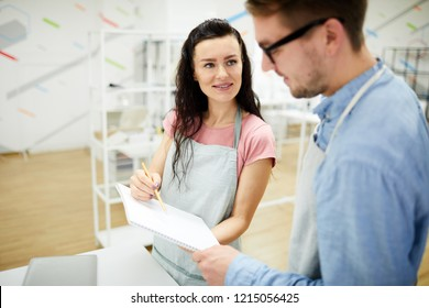 Smiling beautiful brunette woman in apron holding sketchpad and drawing fashion sketch for professional tailor while demonstrating her ideas and skill in workshop