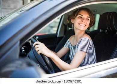 Smiling beautiful brunette woman driving a car
