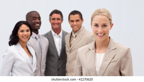Smiling beautiful businesswoman leading her team against white background