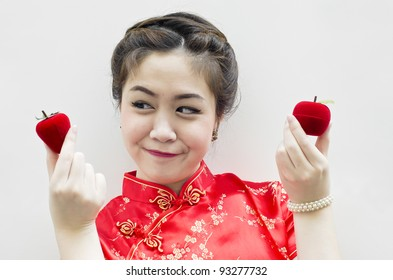 smiling beautiful chinese woman holding a strawberry and an apple