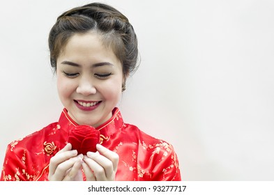 smiling beautiful chinese woman staring at the rose