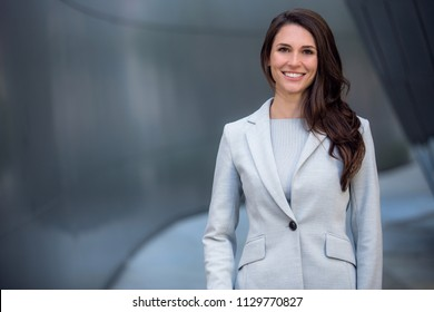 Smiling beautiful commercial model business woman professional entrepreneur in a suit with copy space