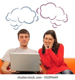 Smiling beautiful couple sitting on a sofa using laptop and dreaming about new home