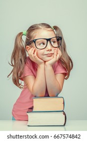 smiling beautiful cute little girl leaning on thick books