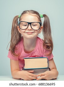 smiling beautiful cute little girl leaning on thick books while looking at camera