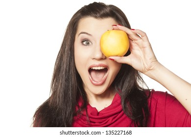 smiling beautiful dark-haired girl with blue eyes showing yellow apple