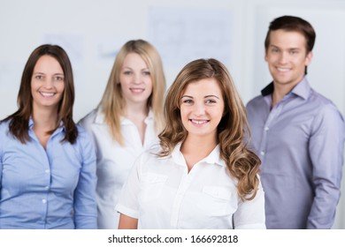 Smiling beautiful enthusiastic young businesswoman posing with her colleagues in the background at the office