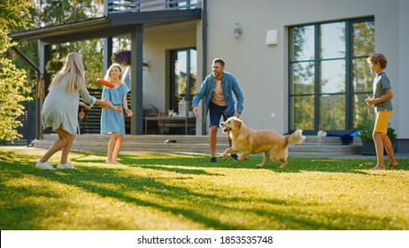 Smiling Beautiful Family of Four Play Fetch flying disc with Happy Golden Retriever Dog on the Backyard Lawn. Idyllic Family Has Fun with Loyal Pedigree Dog Outdoors in Summer House Backyard - Shutterstock ID 1853535748