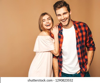 Smiling Beautiful Girl and her Handsome Boyfriend laughing.Happy Cheerful Family.Valentine's Day. Posing on beige wall. Hugging