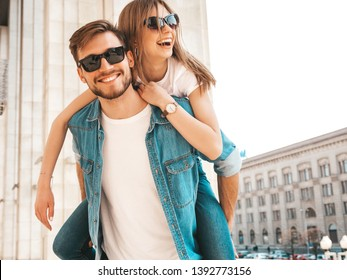 Smiling beautiful girl and her handsome boyfriend in casual summer clothes. Man carrying his girlfriend on the back and she raising her hands.Happy cheerful family having fun on the street background
