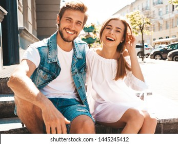 Smiling beautiful girl and her handsome boyfriend. Woman in casual summer dress and man in jeans clothes. Happy cheerful family. Sitting on stairs on the street background.Hugging couple