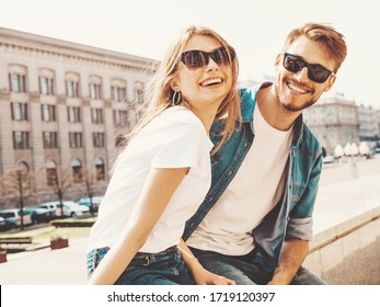 Smiling beautiful girl and her handsome boyfriend in casual summer clothes. Happy cheerful family having fun on the street background in sunglasses