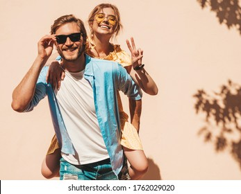 Smiling beautiful girl and her handsome boyfriend. Woman in casual summer dress and man in jeans.Happy cheerful family. Female having fun in the street near wall.Male gives piggyback riding