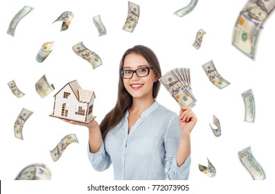 Smiling beautiful girl holding cash and house. Building, mortgage, real estate, sale, finance and property concept. Money rain. Falling hundred dollar banknotes isolated on white background.
