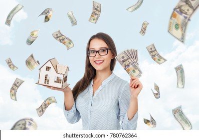 Smiling beautiful girl holding cash and house. Building, mortgage, real estate, sale, finance and property concept. Money rain. Falling hundred dollar banknotes on background of sky.