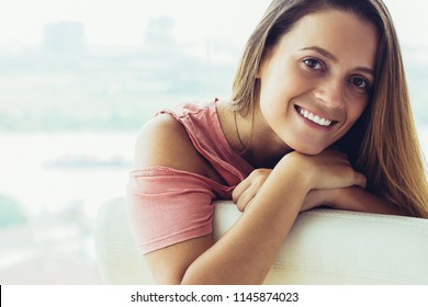 Smiling beautiful girl looking at camera and leaning on chair at home. Portrait of carefree young woman living in big city. Happy woman concept