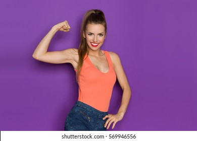 Smiling beautiful girl in orange tank top and jeans shorts flexing biceps and looking at camera. Three quarter length studio shot on purple background..