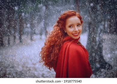 Smiling beautiful girl with red curly hair in red cloak walk in winter forest. Historical reconstruction of ancient Celtic times.