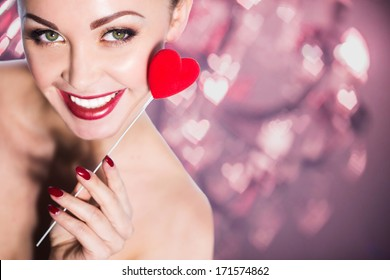 smiling beautiful girl with red heart on bokeh lights background