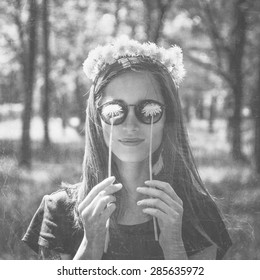 Smiling beautiful girl in wreath of dandelions closed her eyes with dandelions in summer park, concept of summer mood. Black and white image