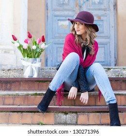 smiling beautiful glamour woman in a hat outdoor with spring flowers in the bucket