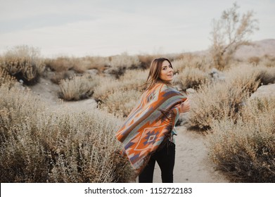 Smiling, beautiful hipster traveler girl in gypsy look and windy hair, in desert nature.  Artistic photo of young hipster traveler girl in gypsy look, in Coachella Valley